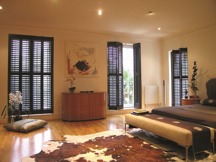 Dark wood shutters by Apollo Blinds. Wooden shutters. Living room shutters. Modern window dressing. Cow skin rug. Contemporary living room design inspiration.