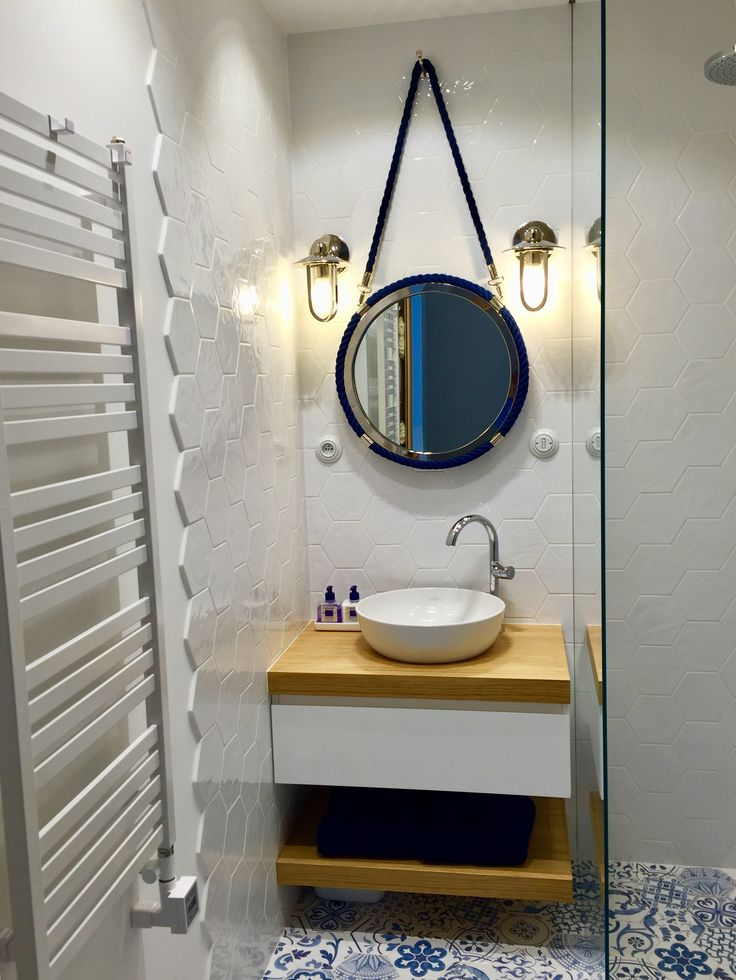 White hexagonal tiles. Blue decor hexagonal floor tiles. Wooden wash basin. Modern shower. Blue rope mirror. Marine style lamps.