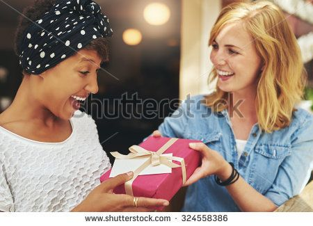 Pretty young blond woman giving an attractive young African American friend a surprise gift gift-wrapped with red paper, a bow and card