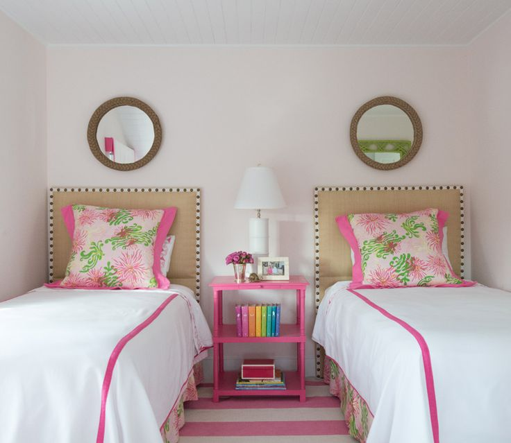 Pink shared girlsu0027 bedroom boasts pale pink walls accenting a pink striped  rug placed beneath twin beds dressed in pink and green bedskirts  complementing