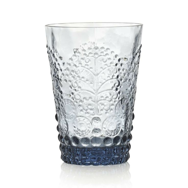 Versatile tumbler is crafted of smoky blue glass, molded with lively embossed hobnails, disks and botanical flourishes to enhance servings of wine, water, soft drinks, and juice | domino.com