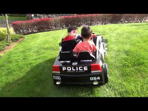 the boys patrolling the yard in their ride on dodge charger police car