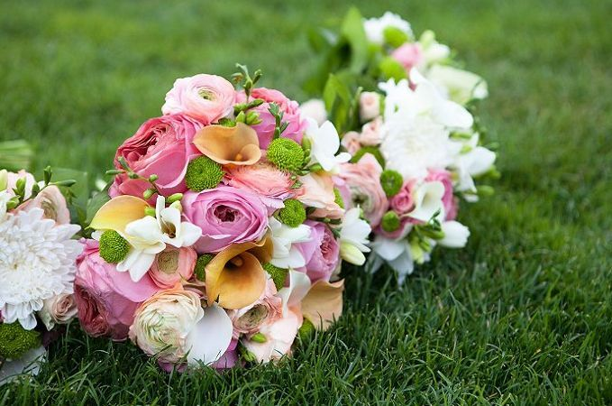 Bridal bouquet with pink garden roes, peach calla, ranacualas, white freesia and green mums