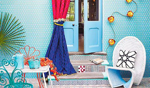 Colourful modern garden patio with geometric wallpaper, multicoloured curtains and white wicker chair
