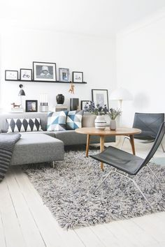 Geometric pattern cushions on a grey corner sofa. Loving the picture shelves behind, too.