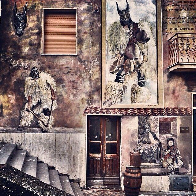 """Ottana. """"Foto vincitrice del challenge. #muralesdisardegna Complimenti a @manu1380 che ha immortalato la facciata della bottega artigiana di Franco Maritato, un ragazzo che ha lasciato il suo lavoro di operaio e si è dedicato completamente alla realizzazione delle maschere tipiche di #Ottana. 'Sas Carazzas' vengono indossate da #Boes, #Merdules e Sa #Filonzana, anch'essi raffigurati nel bel #murale""""."""