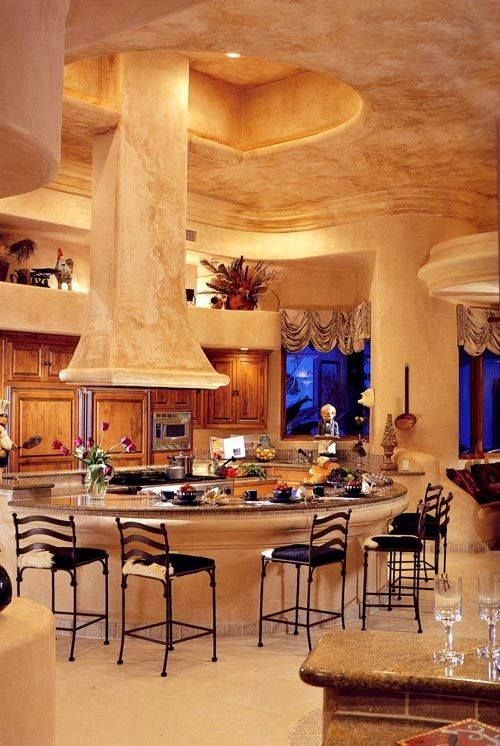 """This enormous kitchen, with drop hood from the ceiling a stone soffit makes this dream kitchen seem """"underground""""."""