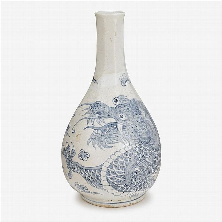 A Korean blue and white faceted bottle vase, joseon dynasty, 19th century, of ovoid form with eight facets to neck flaring to a lipped rim, painted to body in underglazed-blue to show a dragon chasing a flaming pearl. H: 11 3/4 in.