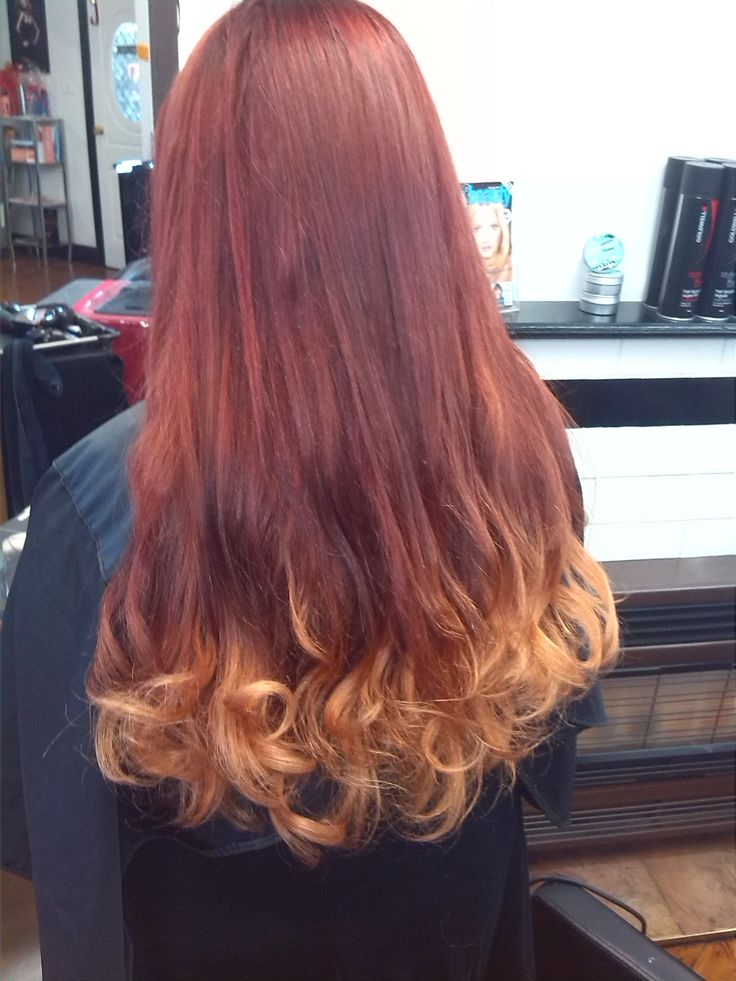 Red and copper balayage on long hair, with some soft curls.