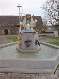 This is the so-called 'Narrenbrunnen' (Fools Fountain) located at the Le-Lion-d'Angers-Platz in Bad Buchau, Germany, Baden-Württemberg. It shows the traditional figures of the local carneval club.