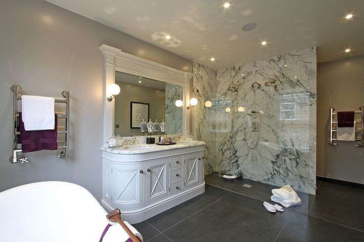 Glamorous bathroom features freestanding bathtub under stainless steel towel warmer mounted on gray walls beside a curved sink vanity with x trim molding on cabinet doors topped with white marble framing his and her sinks under vanity mirror adorned with molding illuminated by globe sconces.