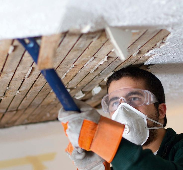 Man wearing a face mask bringing down a sagging lath and
