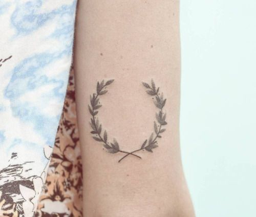 Hand poked laurel wreath tattoo on the back of the right arm....
