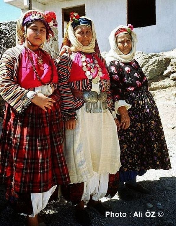 ÇOMAKDAĞ (near Milas, Muğla province): Yörük wedding. A touristic (close to authentic) event organised for tourists. Three women in the festive traditional outfit of the village.  The 'Yörük' are a Turkish group of people, some of whom are (semi-)nomadic, primarily inhabiting the mountains of Anatolia and partly Balkan peninsula.  Yörük maintain in general some association with nomadic life, are poorer (mostly) than average, and all of them are Sunni (unlike the Türkmen, who can be Alevi).