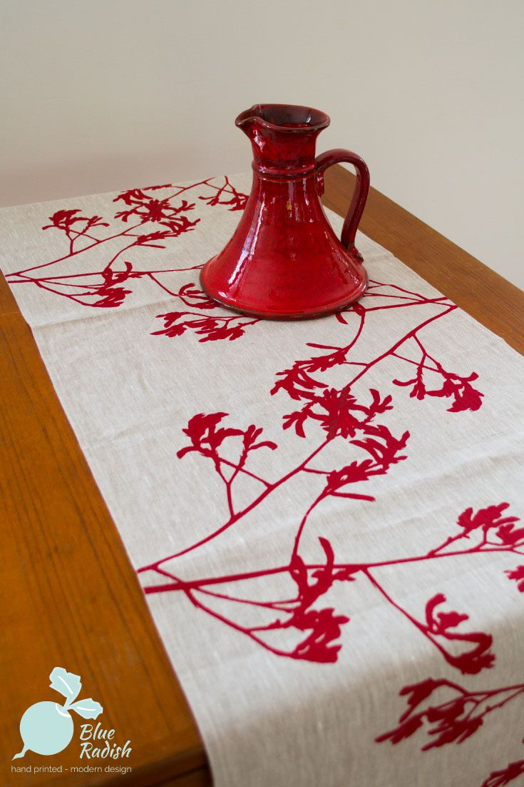 100% linen table runner. Hand printed kangaroo paw design in red ink onto natural coloured linen. Measures approximately 150cm by 45cm.