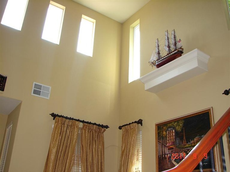 Floating shelf high up on a vaulted ceiling wall.
