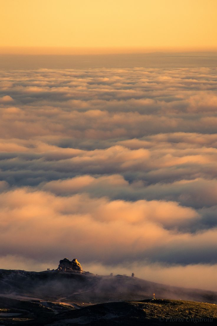 Solitude - Sunset view with a sea of clouds surrounding the Sphinx of Bucegi, a…