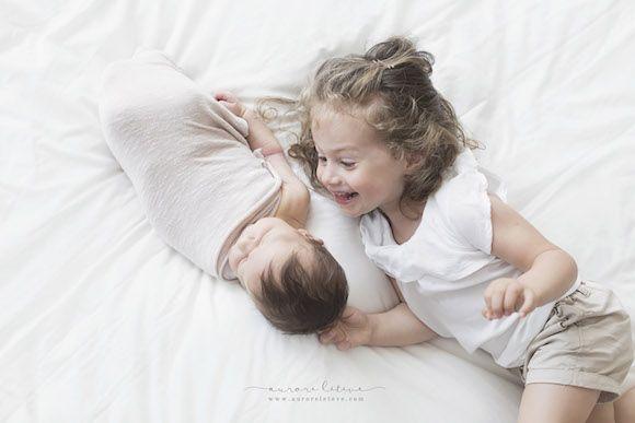 Une petite fille regarde son petit frère nouveau-né prénommé Paul