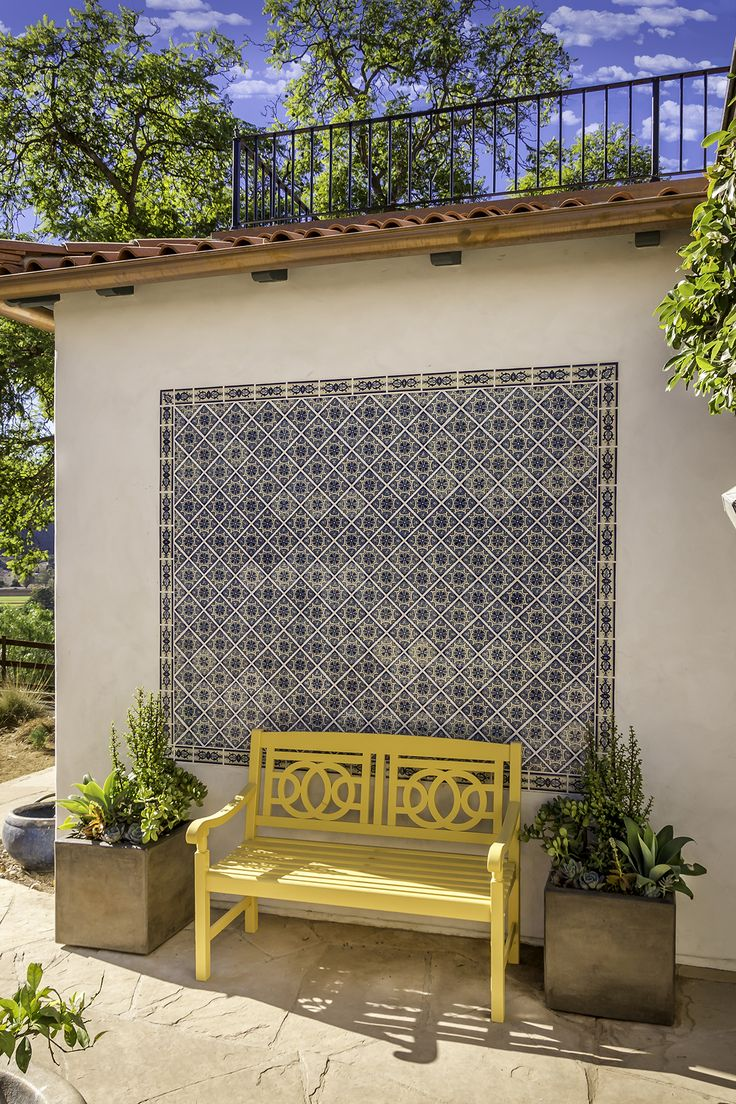Traditional Spanish elements like the terra-cotta roof tiles and Tierra Y Feugo Portici tile mural are complemented by the bright and vibrant bench and modern concrete planter boxes.