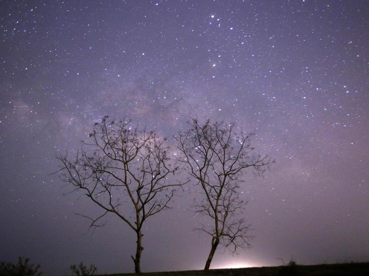 This long-exposure photograph taken on April 23, 2015, on Earth Day, shows Lyrids meteors shower passing near the Milky Way in the clear night sky of Thanlyin, Myanmar.