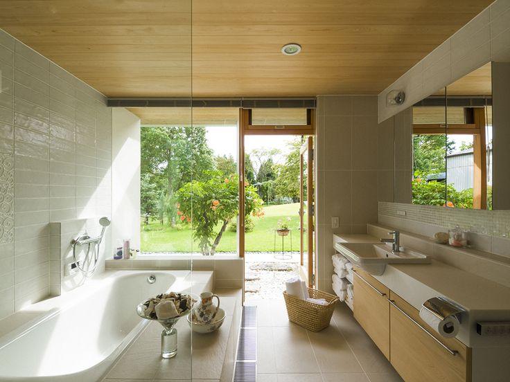 広い庭を一望するバスルーム。庭との間にノウゼンカズラを植えてプライバシーのコントロールとともに景色に奥行きを出す。