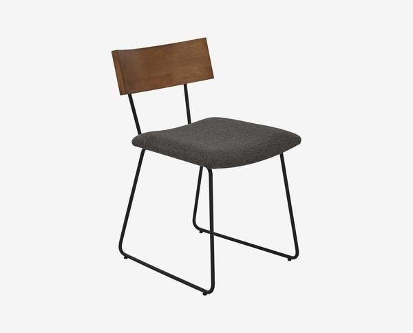 Complete your rustic industrial dining room with the Karsten dining chair. Sleek black metal shapes the connected base. The wood backrest and cushioned seat ensure your comfort, as does the footrest bar.