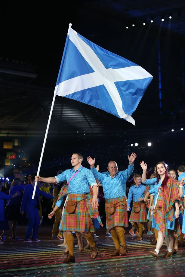 Euan Burton carries the flag as Team Scotland arrive during the 2014 Commonwealth Games Opening Ceremony