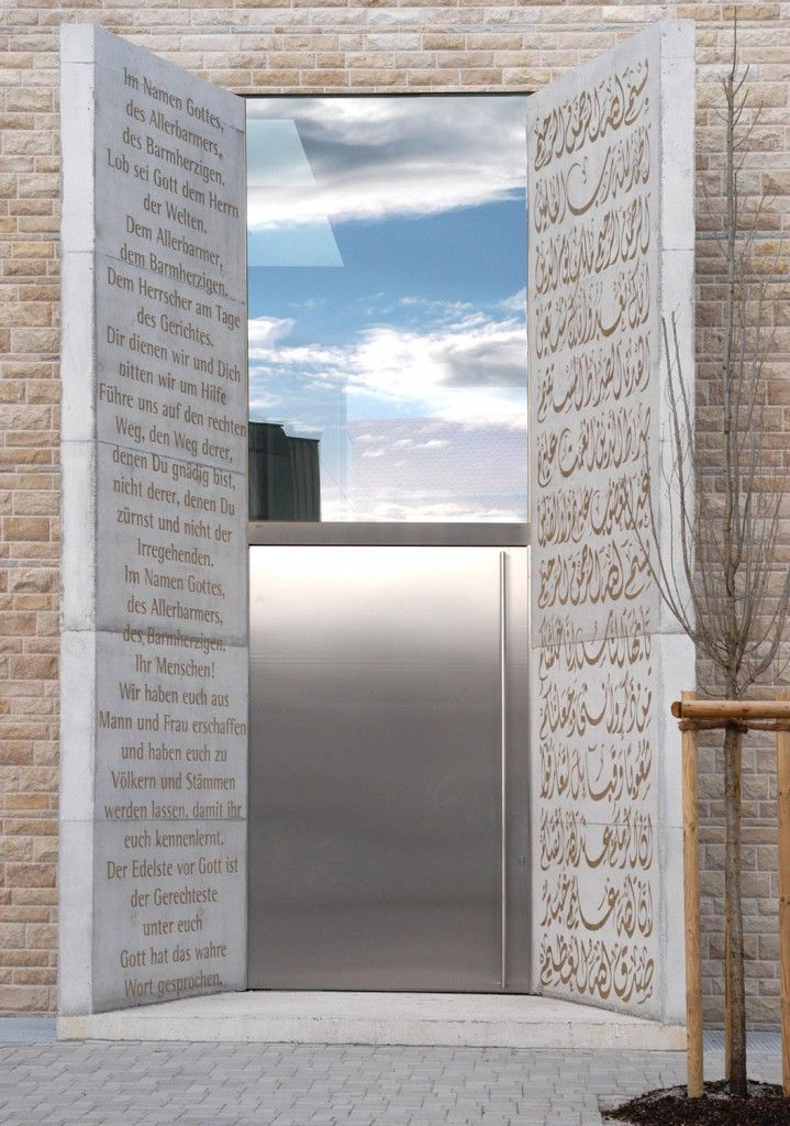 Islamic Forum of Penzberg, Germany, built in 2005 and designed by Alen Jasarevic. Entrance features a stainless steel door and two concrete slabs that swing out, welcoming visitors in German and Arabic script.