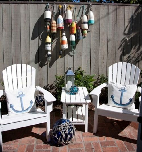 Nautical Patio: http://www.completely-coastal.com/2016/07/small-nautical-theme-cottage-nantucket-style.html Fun nautical theme sitting area with Adirondack chairs, anchor pillows, buoys hanging, and huge glass float... and of course a lantern!