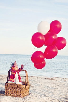 first birthday photography by Laura Mitchum of girl with pink balloons on beach of Florida Keys