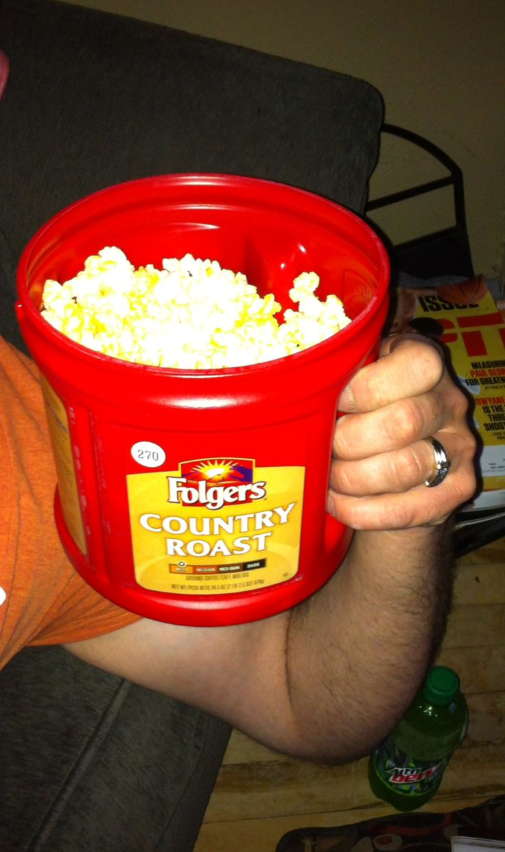 My husband thinks he has found the best popcorn bowl ever. Folger's plastic coffee container-handles and a stay fresh lid.