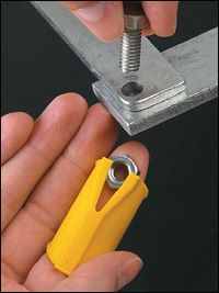 """Finger Wrench -- You know immediately that you could have used this tool hundreds of times in the past. Every time you have to hold a small nut or bolt (it holds either) in an awkward spot, this wrench works marvellously. Finger pressure holds the nut or bolt in the wrench, while the raised, tapered slot prevents it from turning. Made from high-impact ABS, the sleeve adjusts to fit any size of finger. Holds all nuts up to 1/2"""" Price: $3.95"""