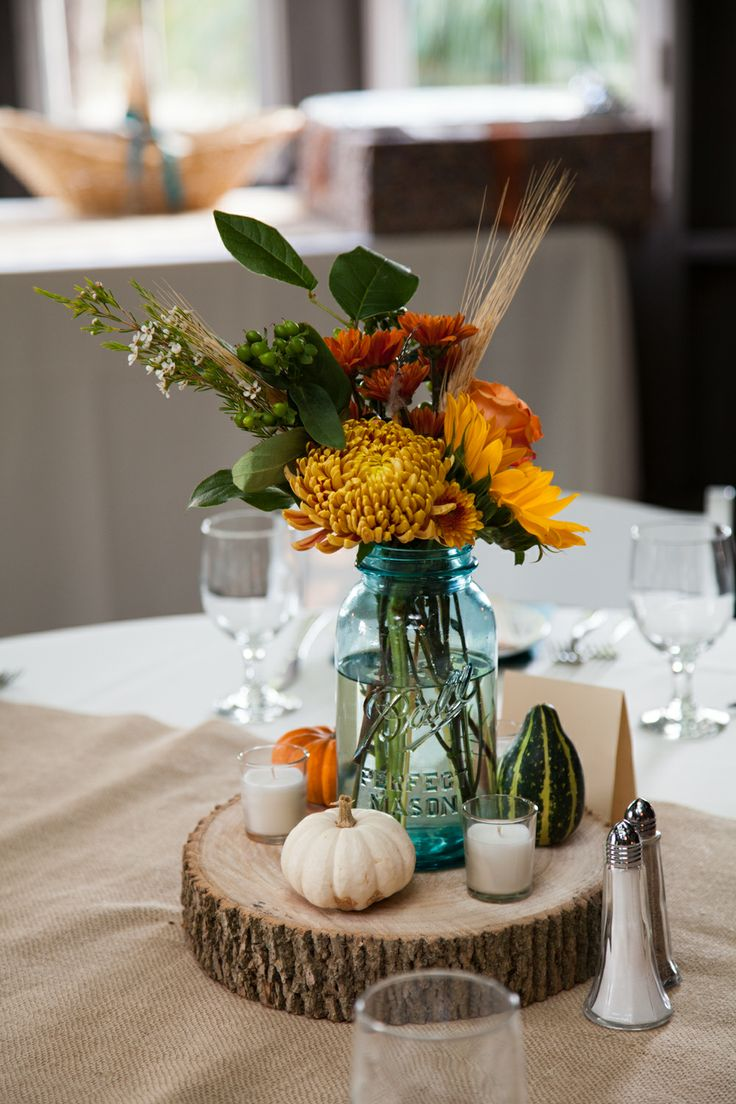 The centerpiece. Burlap runner, wooden cookie, blue mason jar filled with season flowers of football mums, sunflowers, hardy mums, wheat, open roses, and foliage.  Accented by mini gourds.