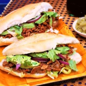 Chile Colorado beef sandwich served on a toasted bolillo roll with red onion, avocado, and cilantro.
