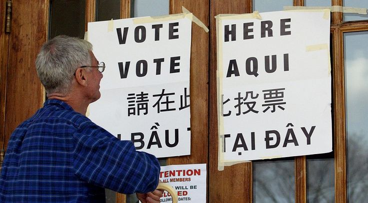 "Joe McLauglin puts up ""vote here"" signs in multiple languages outside a polling station in the Jamaica Plain section of Boston."