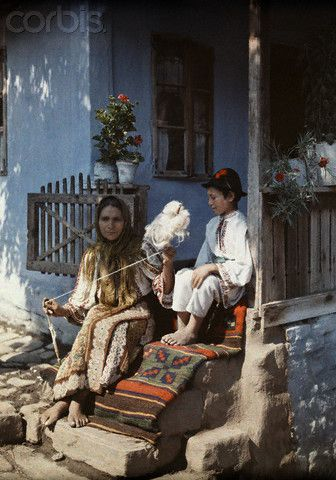 A child watches as the woman twists wool to begin making a rug, Romania, c. 1934