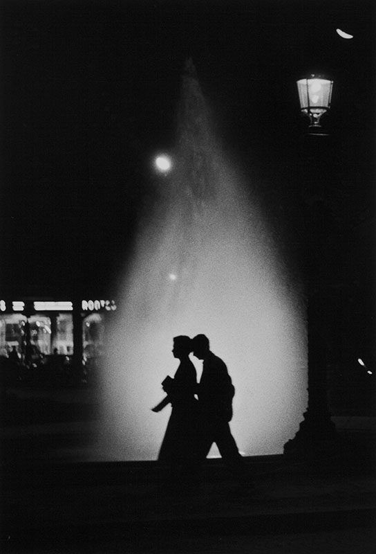 At night, a couple passes by the illuminated fountains of the Champs-Élysées roundabout – Janine Niepce