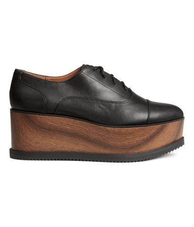 Svart. Ett par oxfordskor i läderimitation med hög platå i träimitation. Skorna har spetsig tå och sluten snörning. Foder och innersula i läderimitation.