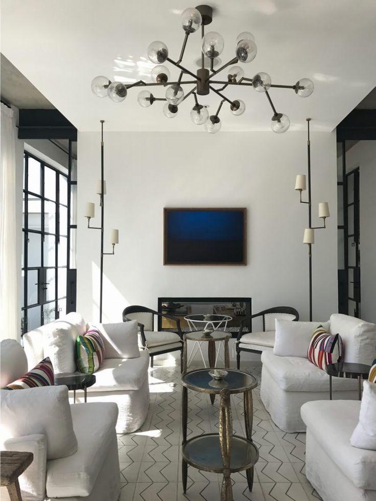 Una sala con sillones blancos, cojines de colores y rayas, mesas de centro originales y vintage, dos lámparas de piso modernas y una lámpara de techo moderna. El arte también le da un toque gracias a su look moderno.