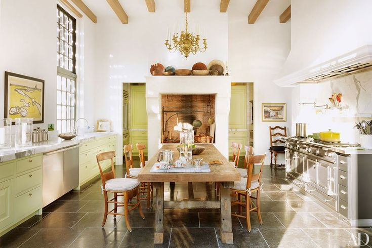 Antique French chairs surround the kitchen table; the range is by La Cornue.
