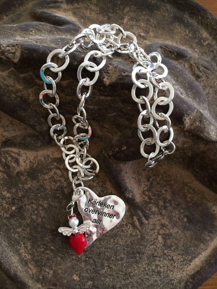 Halsband med ängelberlock och hjärta med text: kärleken övervinner allt. Necklace with angelcharm and heart with lettering: love conquers all. Sams design handmade