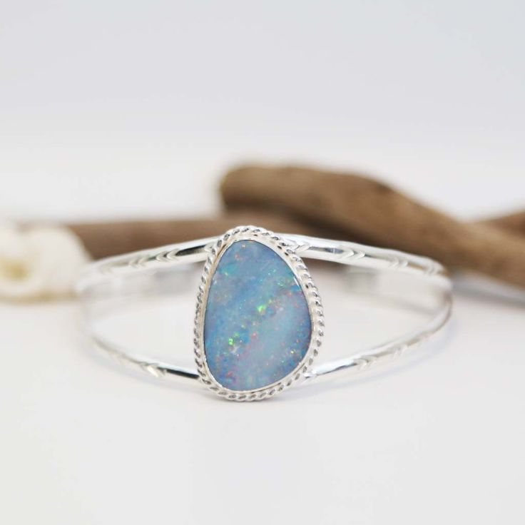 Stamped Opal Cuff >> This Opal Cuff is featured with a large stunning Australian Opal Doublet with twisted sterling silver settings. The opal itself is definitely an impressive piece that we make into a cuff so far.The fire inside the opal resembles our mysterious Galaxy.Hand Stamped arrow mark on the cuff band makes it more intricate.