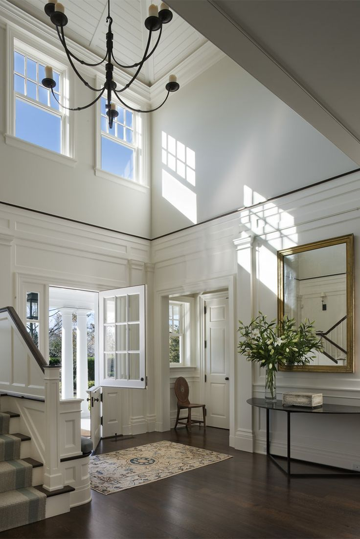 Love two-story entryways and all the white woodwork.