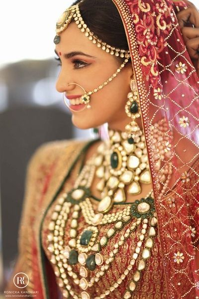 layered heavy polki jewellery with kundan jade and emerald stones, choker raani haar, elaborate bridal jewellery, delicate nose ring and nath