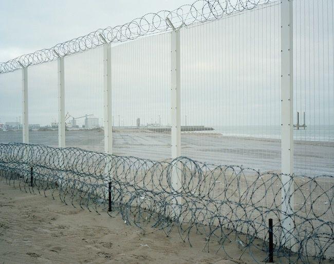 Calais, 29 km d'un dispositif de haute sécurité : une clôture de 4m de haut surmontée de fil barbelé concertina arborant des lames de rasoir clôt tous les accès au au port et au terminal d'Eurotunnel. Ici sur la plage au nord de la ville vers l'accès au p - Crédit photo : MURATET Myr