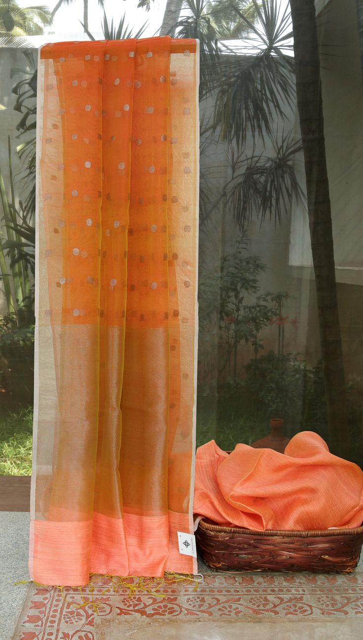 This Orange coloured Bailou is a matka silk sari. This borderless sari comes with a light orange kora pallu with silver polka dots and stripes making it perfect for daywear.