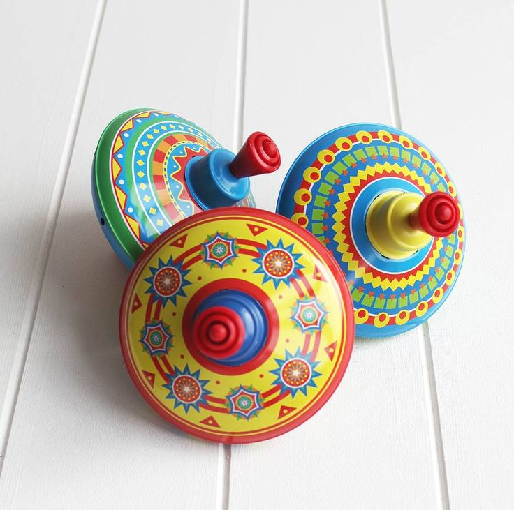 A quality made tin version of the traditional children's spinning top.for suitable for children under 36 monthsThese lovely spinning tops are decorated with a spectrum of colours which creates a rainbow effect when spinning. They are inspired by folk art from the circus and fairground. They are able to spin on any hard flat surface with the plastic base preventing it from marking or damage to the surface. This is the perfect addition to any child's playroom and makes a great keepsake gift…