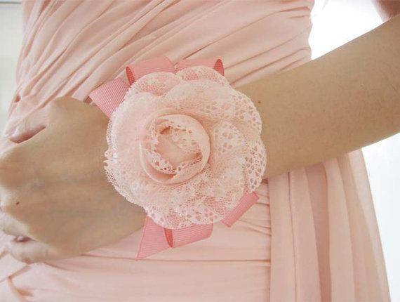 These bridesmaid wrist corsages / groomsman boutonnieres are made by high profile creamy pink simulated silk sheer roses and dark pink ribbons