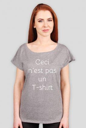 """Ceci n'est pas un T-shirt dla niej  Porzuć zwykłe koszulki! Załóż oryginalną koszulkę nie-koszulkę! Wprowadź przechodniów na ulicy w stan filozoficznego zdumienia, aby na chwilę wybić ich z wyścigu szczurów, w którym biorą udział na co dzień!   """"Ceci n'est pas un T-shirt"""" (dosł. To nie jest T-shirt) to parafraza znanego obrazu Magritte'a """"Ceci n'est pas une pipe"""".    Dzięki unikalnemu projektowi Twoje codzienne wygodne ubranie nabierze innego wymiaru!   Wyraź  swoją niepowtarzalność!"""