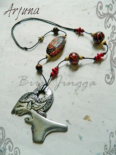 Traditional theme. Metal pendant and wooden beads from jogjakarta, indonesia.